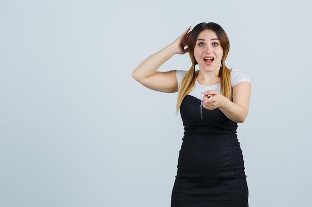 Giovane donna che tiene la mano sulla testa e indica