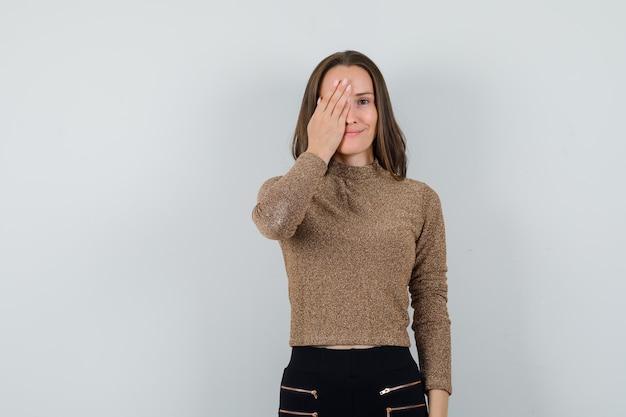 Giovane donna che tiene la mano sul suo occhio in camicetta dorata, vista frontale.