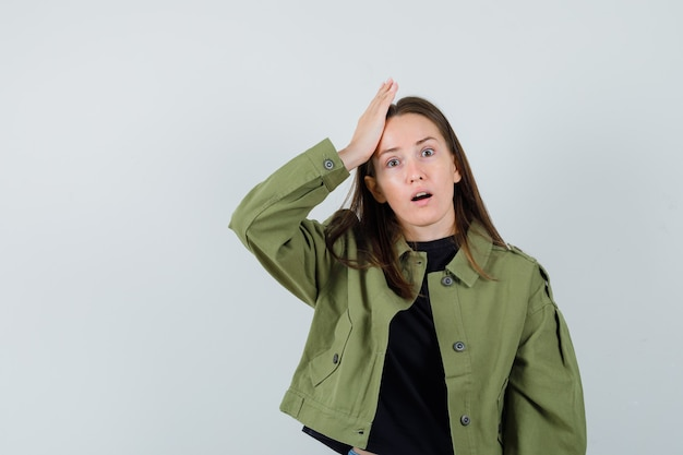 Young woman holding hand on her head in green jacket and looking worried , front view.