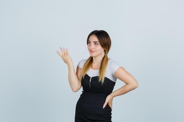 Giovane donna che tiene la mano sull'anca mentre allunga la mano in modo interrogativo