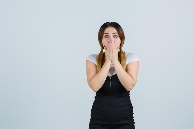 Giovane donna che tiene la mano sulla bocca e sembra perplessa