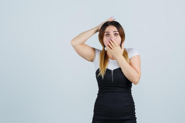 Giovane donna che tiene la mano sulla bocca mentre tiene la mano sulla testa