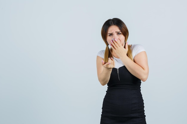 Giovane donna che tiene la mano sulla bocca mentre indica te