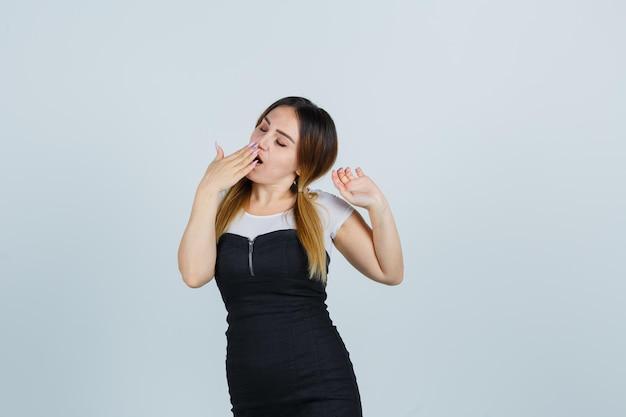 Giovane donna che tiene la mano sulla bocca mentre sbadiglia