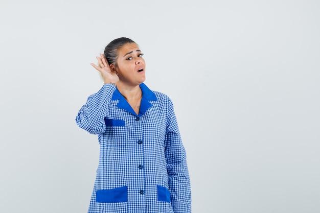 青いギンガムチェックのパジャマシャツを着た誰かの話を聞いて集中しているように耳の近くで手をつないでいる若い女性。正面図。
