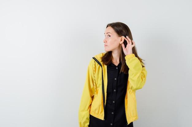 何かを聞くために耳の近くで手をつないでいる若い女性
