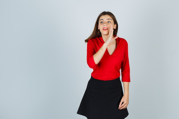 Young woman holding hand near mouth as telling secret in red blouse