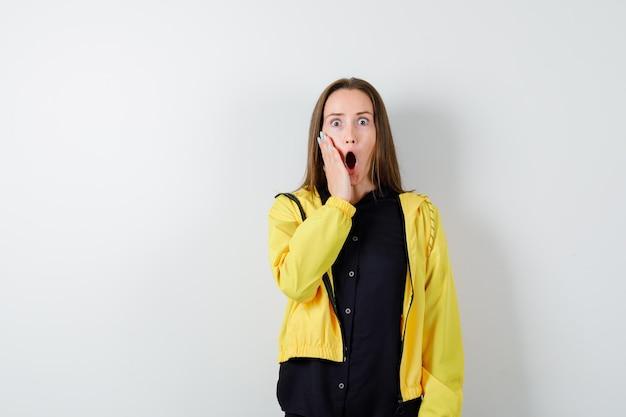 Молодая женщина, держащая руку возле рта в шоке