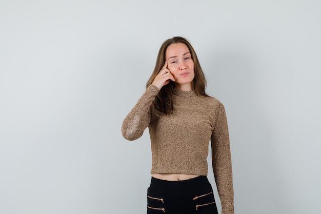頬に手をつないで、金色のセーターと黒のズボンで正面にポーズをとって、魅力的に見える若い女性