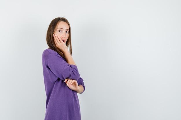 보라색 셔츠에 뺨에 손을 잡고 놀 찾고 젊은 여자. 전면보기.