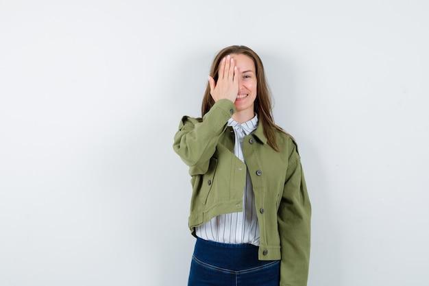 Молодая женщина, взявшись за глаза в рубашке и глядя веселый, вид спереди.