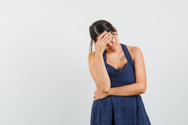 ドレスを着て額に手を握り、苦しんでいるように見える若い女性