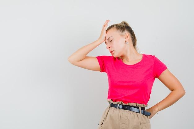 젊은 여자 t- 셔츠와 바지에 이마에 손을 잡고 우울 찾고