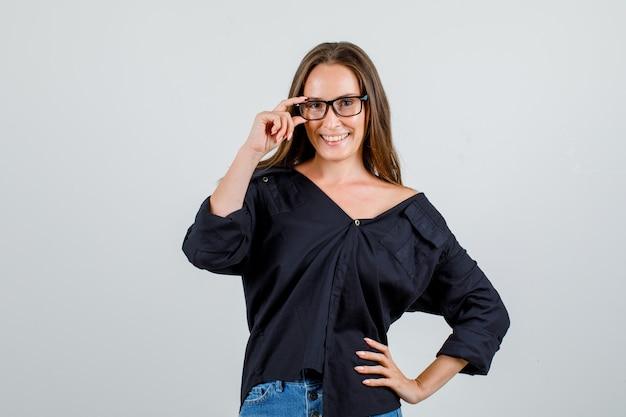 Молодая женщина держит руку на очках в рубашке, шортах и выглядит веселой. передний план.