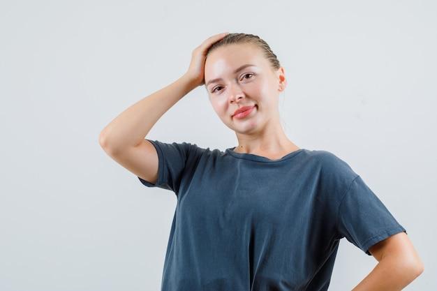 頭に手をつないで、灰色のtシャツの正面図で笑っている若い女性。