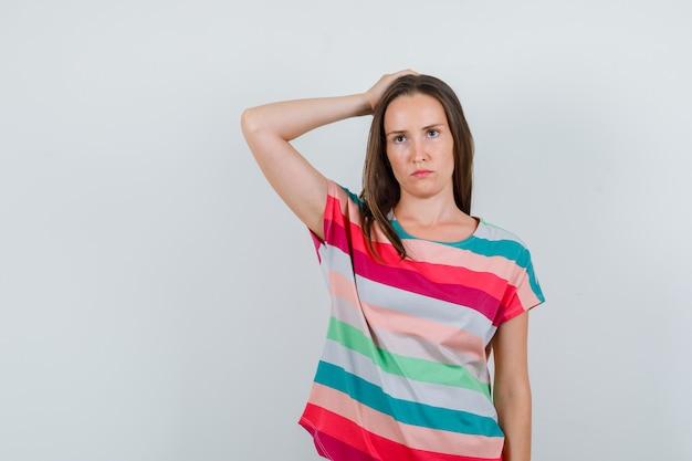 Tシャツを着て頭に手をつないで陰気な若い女性。正面図。