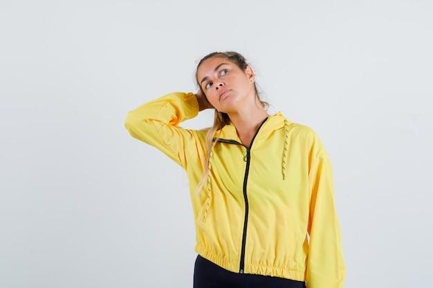노란 우비를 입고 멀리보고 집중하는 동안 머리에 손을 잡고 젊은 여자