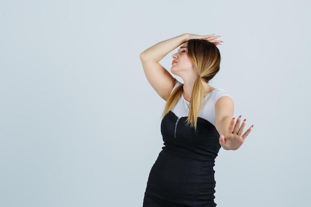 停止ジェスチャーを示している間、頭に手をつないでいる若い女性