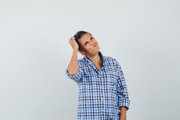 체크 무늬 셔츠에 생각 하 고 의아해 찾고있는 동안 머리에 손을 잡고 젊은 여자.