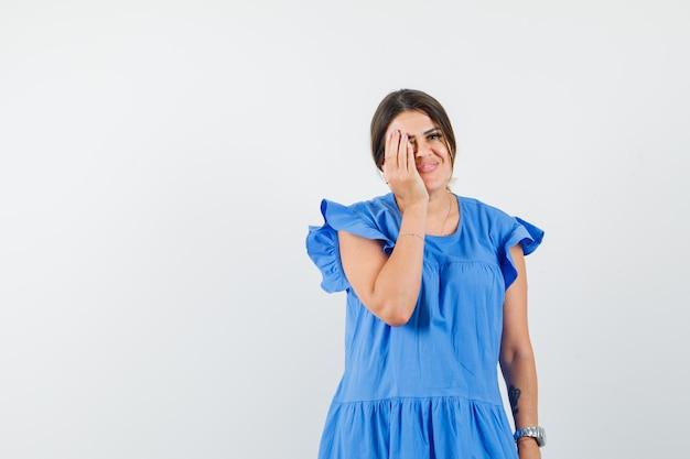 파란 드레스에 눈에 손을 잡고 기쁜 찾고 젊은 여자