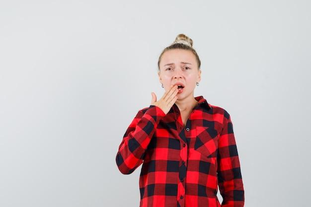 チェックシャツで開いた口に手をつないで、心配そうに見える若い女性