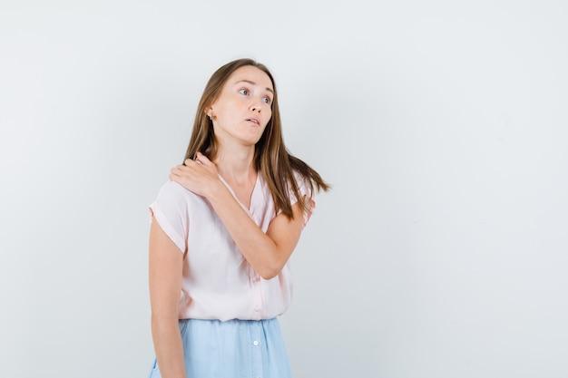 Tシャツ、スカート、物思いにふける、正面図で肩に手をつないでいる若い女性。