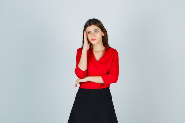 寺院に手をつないで、赤いブラウスで何かを考えている若い女性