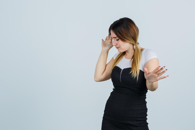 停止ジェスチャーを表示しながらこめかみに手をつないで若い女性