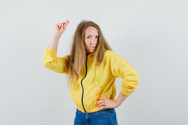 젊은 여자 허리에 손을 잡고 노란색 폭격기 재킷과 블루 진에 카메라에 포즈를 취하고 매력적인, 전면보기를 찾고.