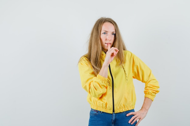 허리에 손을 잡고 노란색 폭격기 재킷과 블루 진에 침묵 제스처를 보여주는 젊은 여자와 심각한 찾고. 전면보기.