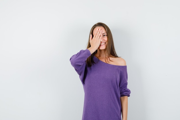 Young woman holding hand on one eye in violet shirt and looking happy. front view.