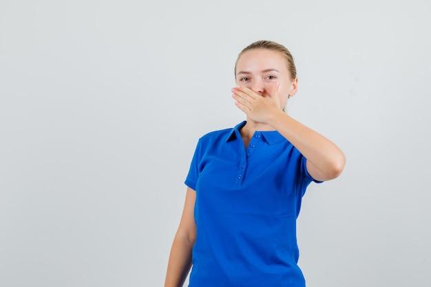 파란색 티셔츠에 입에 손을 잡고 젊은 여자