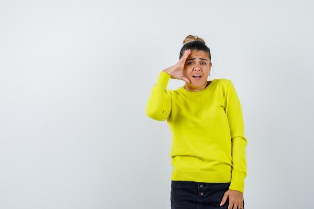 노란색 스웨터와 검은색 바지를 입고 손을 마주 잡고 놀란 젊은 여성
