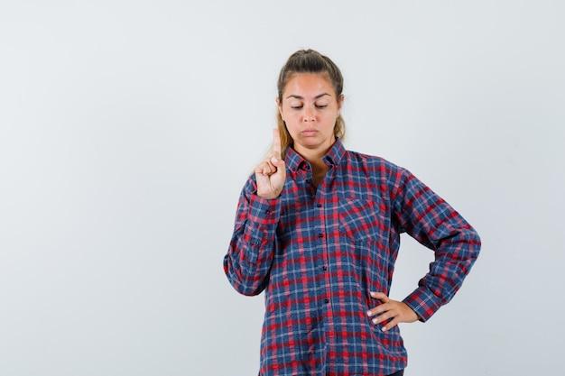 Giovane donna che tiene la mano sulla vita mentre solleva il dito indice nel gesto di eureka in camicia a quadri e sembra seria
