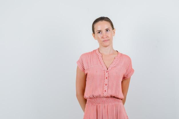 Giovane donna che tiene le mani sulla schiena in abito a righe e guardando pensieroso, vista frontale.