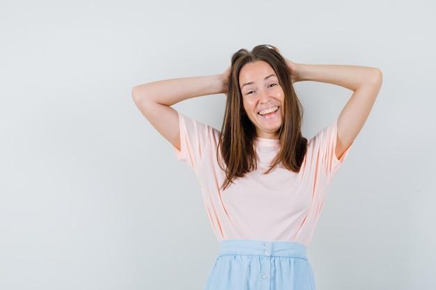 Tシャツ、スカートで頭の後ろに手をつないで、至福の正面図を探している若い女性。