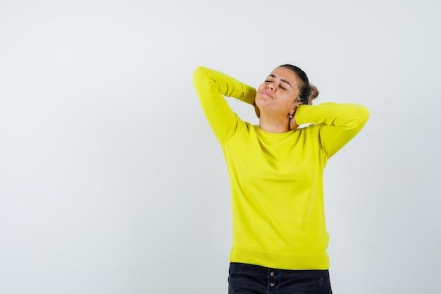 노란색 스웨터와 검은색 바지를 입고 머리 뒤로 손을 잡고 편안하게 보이는 젊은 여성