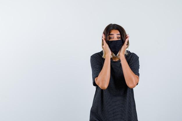 Giovane donna che tiene le mani sulle guance in abito nero, maschera nera e sembra seria. vista frontale.