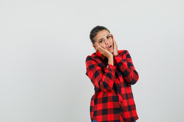Young woman holding hands on cheeks in checked shirt and looking surprised. front view.