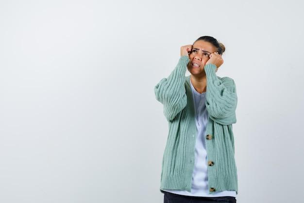 Giovane donna che si tiene per mano alle guance, guardando sopra in maglietta bianca e cardigan verde menta e sembra pensierosa