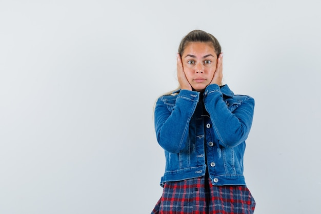 Young woman holding hands on cheeks in shirt, jacket and looking scared. front view.
