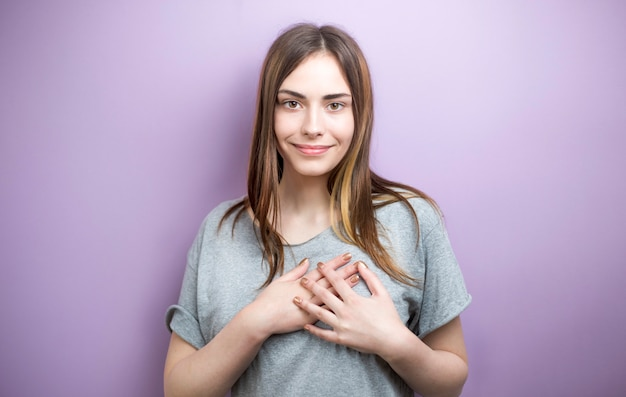 Young woman holding hands on chest feeling pleased thankful.