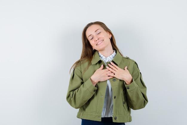Giovane donna che si tiene per mano sul petto in camicia, giacca e sembra grata. vista frontale.