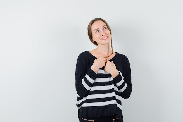 Young woman holding hands over chest and thinking about something in striped knitwear and black pants and looking happy