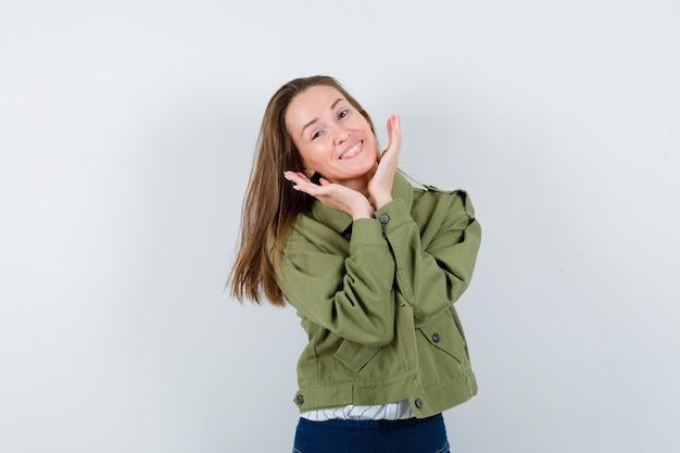 Giovane donna che si tiene per mano sotto il mento in camicia, giacca e sembra carina, vista frontale.