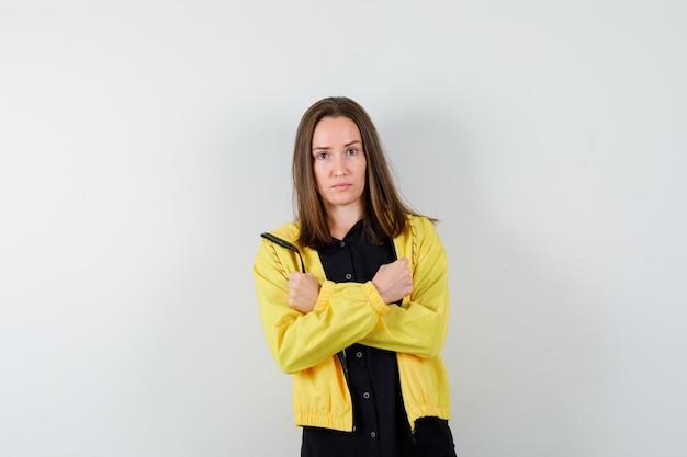 Молодая женщина, держащая скрещенные руки и сжимающие кулаки