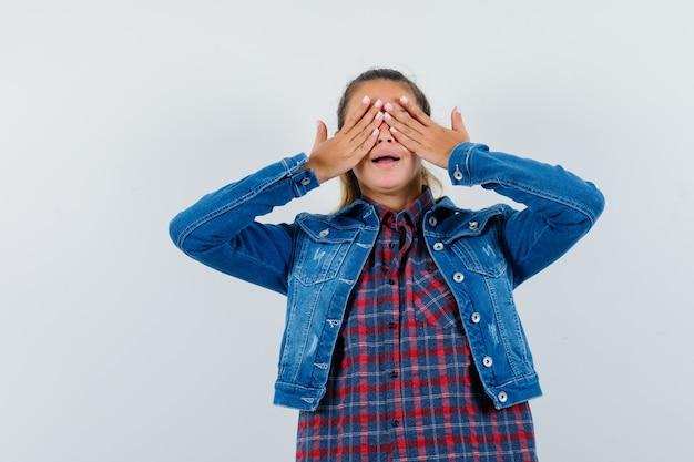 Giovane donna che tiene le mani sugli occhi in camicia, giacca e guardando eccitato, vista frontale.