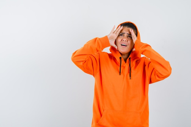 Giovane donna che si tiene per mano a faccia in felpa con cappuccio arancione e sembra concentrata
