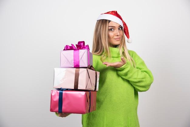 Giovane donna che tiene in mano i regali di natale festivi.