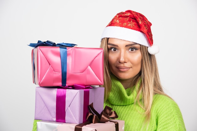 Young woman holding in hands festive christmas presents.